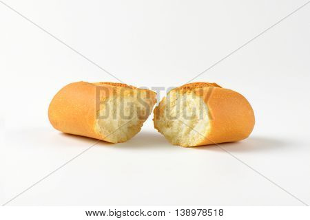halved fresh bread roll on white background