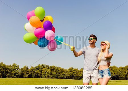 Happy Man And Woman In Glasses Walking With Color Balloons
