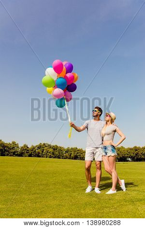 Young Happy Couple In Love Walking In The Park With Balloons