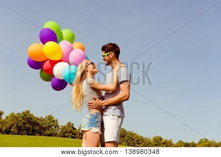 Young Happy Man Huging His Girl And Holding Balloons