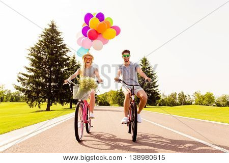 Man And Woman Having Fun On Summer Day And Cycling With Balloons