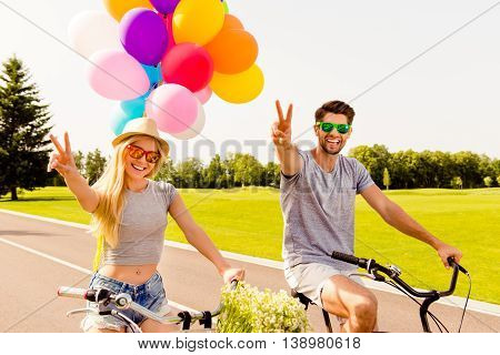Happy Man And Woman Riding Bicycles And Gesturing With Fingers