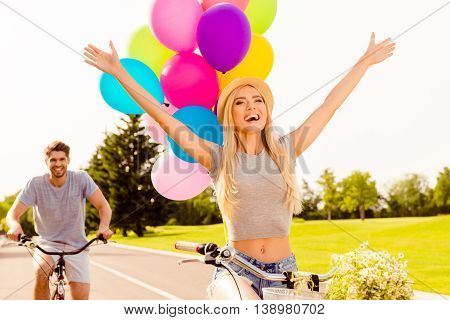 Couple In Love Riding Bicycles. Focus On Girl With Raised Hands