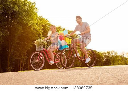 Happy Young Lovely Couple In Love With Balloons Riding Bicycles