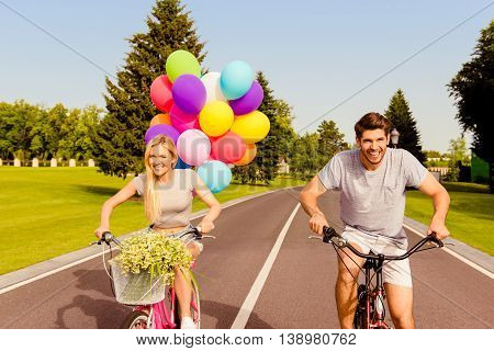 Happy Couple In Love Riding A Bicycle Race With Balloons In Park