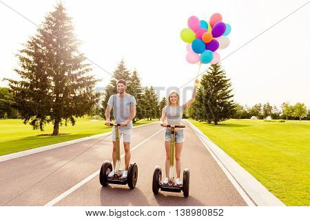 Man And Woman Having Romantic Summer Holiday And Riding Segways In Park