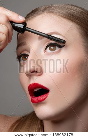 Close up of woman face with mascara brush. Eyes Make up with Perfect Skin