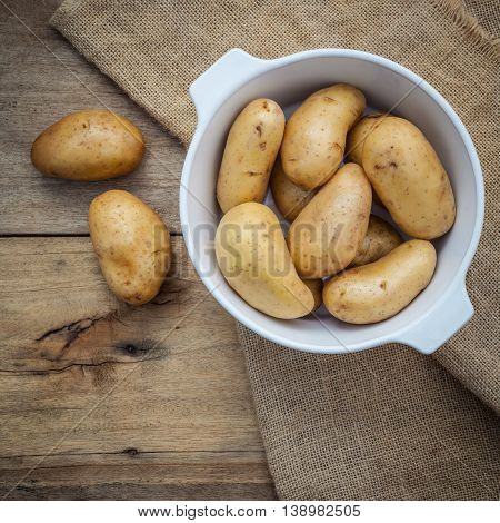 Composition Of Fresh Organic Potatoes In White Ceramic Bowl On Hemp Sake And   Rustic Wooden Table.