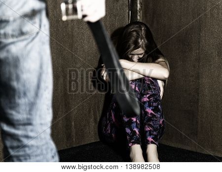 frightened woman sitting in the corner with a faceless man holding a belt, a conceptual shoot portraying the process and effects of domestic violence.