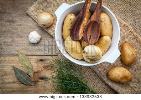 Fresh Organic Potatoes In White Ceramic Bowl With Ingredients And Herbs  Fennel ,garlic,bay Leaves A