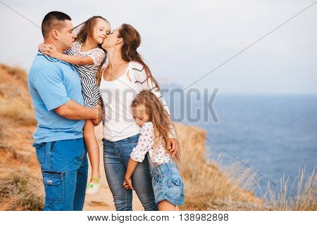 Family walking on the sea shore in sunset, mom kissing daughter