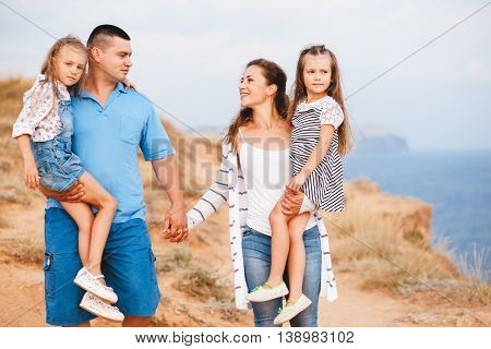 Family walking on the sea shore in sunset, parents holding hands