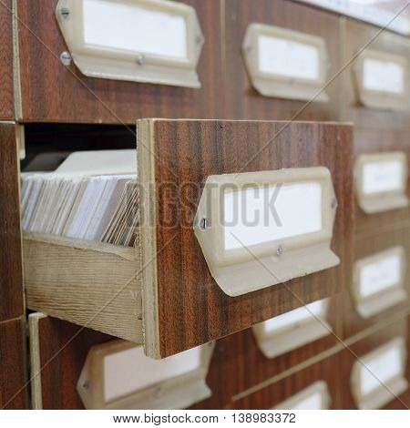 Old wooden card catalog with one opened drawer in library