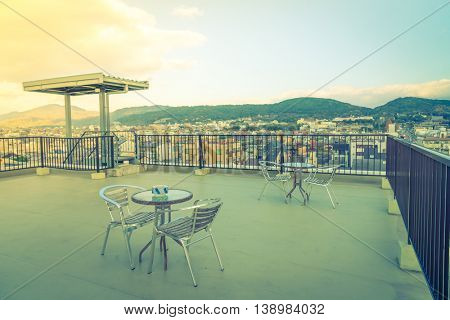 Table and chairs on  roof top terrace exterior  ( Filtered image processed vintage effect. )