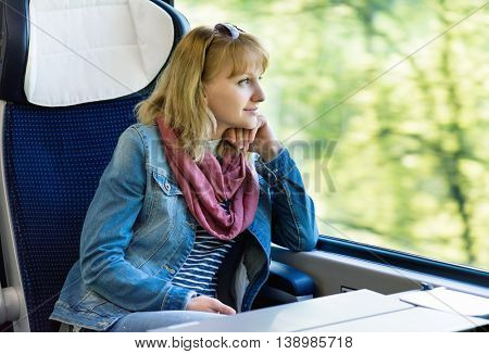 Young pretty woman traveler sitting by train or bus, looking through window