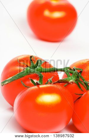 Red  ripe tomatoes on a brunch isolated on a white background.