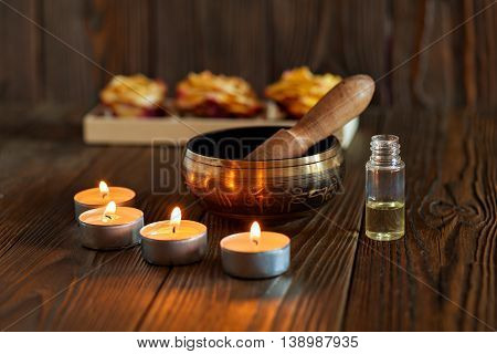 Singing bowl on dark wooden background. Burning candles and oil for aromatherapy and massage
