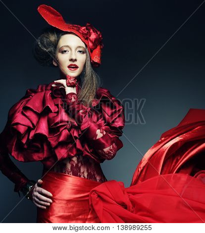Glamour fashion model in elegance red costume with red hat. Studio shot.
