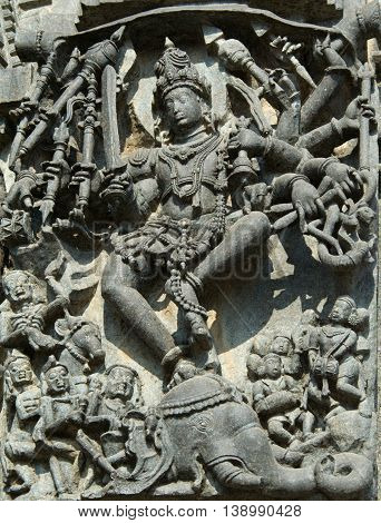 Shiva killing a demon Gajasura appearing in the guise of an elephant by dancing inside and piercing its skin; wall carving in Channakeshava temple at Belur Hassan district Karnataka state India Asia
