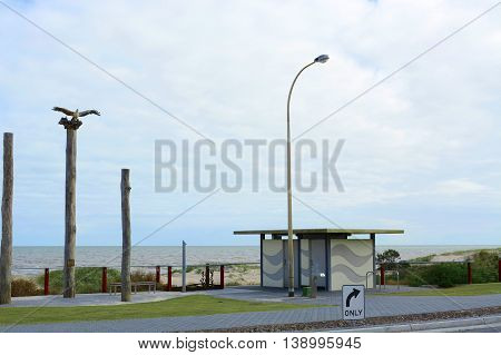 Entrance to Henley Beach South Australia with the sea eagle sculpture on top of wood pylons.