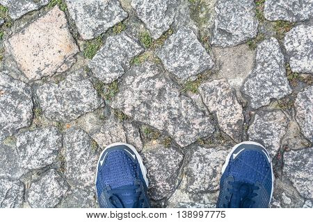 Gray old stone pavement and blue shoes ready to walk into a great journey.