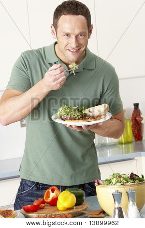 Man Eating Meal In Kitchen