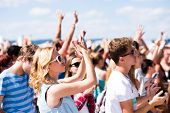 Teenagers at summer music festival under the stage in a crowd enjoying themselves, arm raised poster