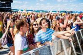 Teenagers at summer music festival under the stage in a crowd enjoying themselves poster