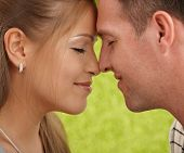 Loving couple's faces in closeup, foreheads touched, facing each other, smiling.? poster