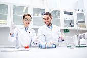 science, chemistry, biology, pharmacy and people concept - young scientists with pipette and flask making test or research in clinical laboratory poster