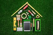 Home renovation remodeling and DIY concept work tools and tablet composing a house shape on the grass poster