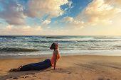 Yoga outdoors on beach - woman practices Ashtanga Vinyasa yoga Surya Namaskar Sun Salutation asana Urdhva Mukha Svanasana - upward facing dog pose on sunset poster