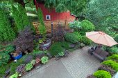 Backyard garden landscaping with paver bricks patio hardscape trees potted plants shrubs pond rocks furniture and red barn poster