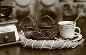 Grinder with coffee beans in copper bowls and Cup with composition of jute poster