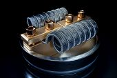 Vaping atomizer with clapton coil. Black background poster