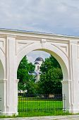 Arcade of the ancient Yaroslav courtyard at summer sunny day in Veliky Novgorod Russia - unusual composition with the St Nicholas Cathedral in one of the arches. Architecture landscape poster