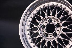 Aluminum metal wheel rim texture. Car alloy wheel, isolated on black background. Classic drive.