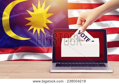Online Vote , Poll, Exit Poll For Malaysia General Election Concept. Close Up Hand Of A Person Casti