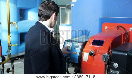 Back View On Engineer Operating Equipment In A Factory. Engineer Looking At The Control Panel In A C