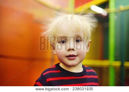 Fanny Hairstyle Of Little Boy After Activity On Trampoline. Child Playing On Indoor Playground. Kid
