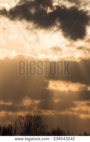 Sunset Background, Sun Behind Dark Cloud With Crepuscular Rays To Tree Top Border. Beautiful Cloudy