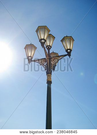 Vintage Old Lantern Isolated On Empty Blue Sky Background On Sunny Summer Day. Historic Lamppost Wit