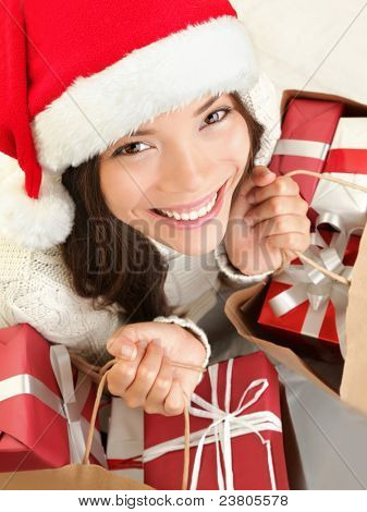 Christmas gift woman shopping wearing santa hat smiling happy. Closeup portrait of cute mixed race Caucasian Asian female model isolated on white background.