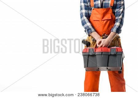 Cropped view of workman in orange overall holding tool box isolated on white poster