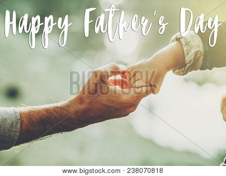 Happy Father's Day Text, Greeting Card Concept. Father And Little Son Holding Hands In Sunlight In S