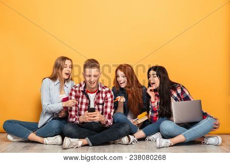 Group of young excited school friends doing homework while sitting on a floor together with laptop computers over yellow background