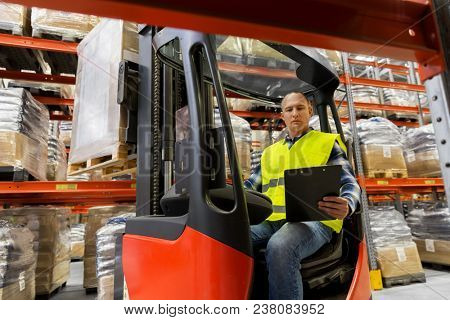 wholesale, logistic, shipment and people concept - loader with clipboard in forklift loading boxes at warehouse