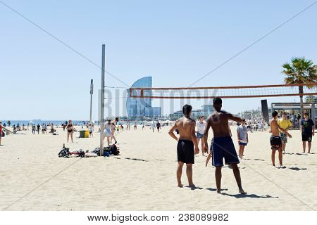 BARCELONA, SPAIN - MAY 7, 2017: People playing volleyball at the Barceloneta Beach in Barcelona, Spain, with the W Hotel, also known as Hotel Vela or Sail Hotel, in the background