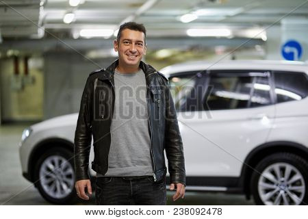 Smiling man in jeans and leather jacket stands in underground parking.