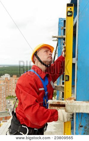 builder worker checking vertical with level tool at construction site